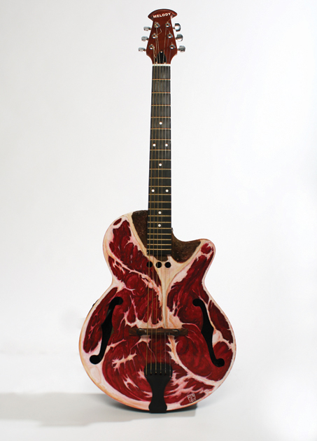 Painting of a steak, on the front of a guitar